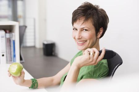 reconocimientos: Mujer comiendo una manzana en su oficina LANG_EVOIMAGES