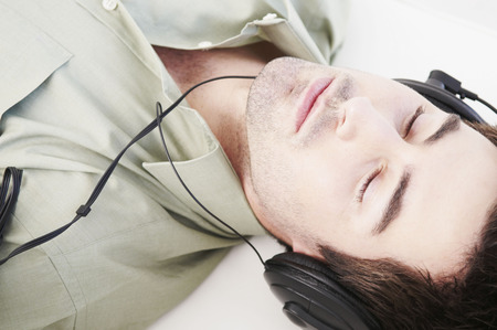 Reclined male relaxes with headphones LANG_EVOIMAGES