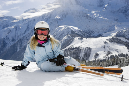 mountainous: Girl with skis lying on the snow LANG_EVOIMAGES