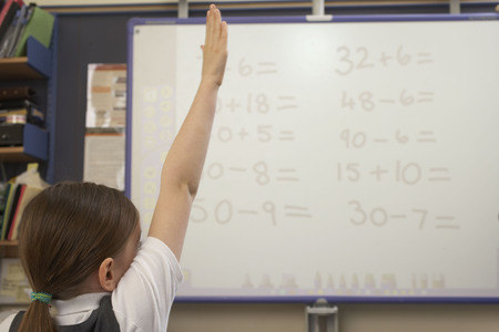Girl raising her hand in classroom LANG_EVOIMAGES