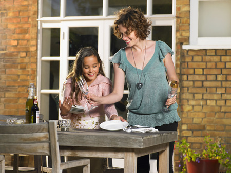 enjoys: Mother and daughter laying table outside