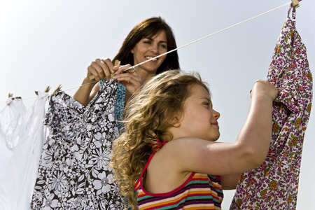 Girl helping mother hang clothes