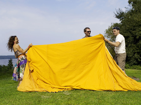 tugging: Three people setting up a tent
