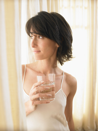 rejuvenated: Woman holding a glass of water