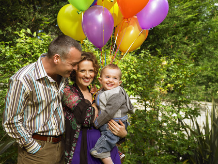 Mother, father and baby with balloons LANG_EVOIMAGES