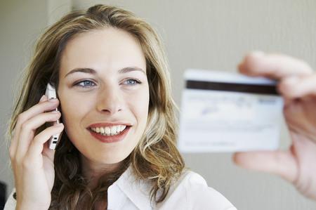reconocimientos: Mujer en el teléfono, mirando la tarjeta de crédito
