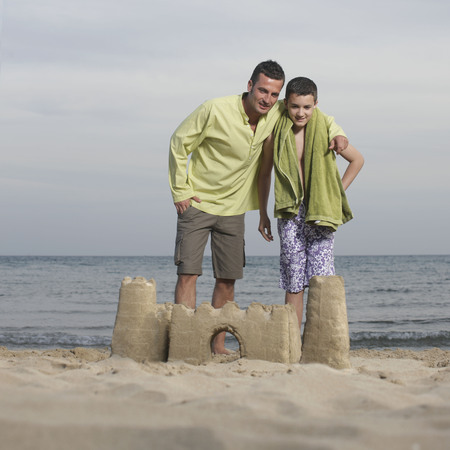 defended: Father and son posing with sandcastle LANG_EVOIMAGES