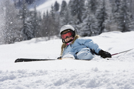 Girl with skis lying on snow LANG_EVOIMAGES