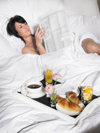 pamper: Woman reading newspaper in bed