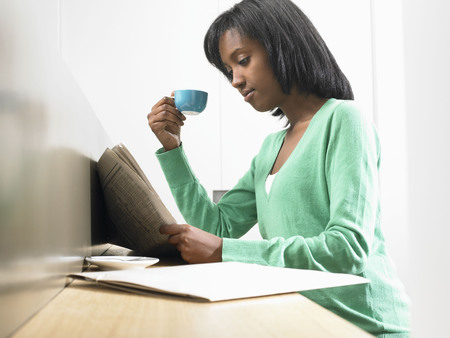 singularity: Woman having a coffee, reading newspaper