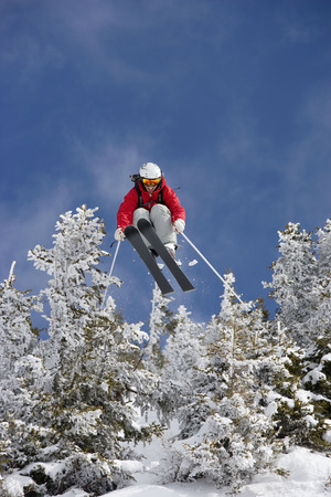 Skier jumping over snow covered trees