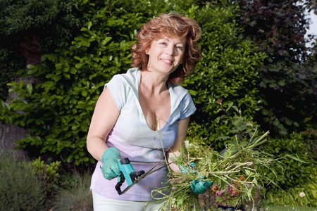 Mature woman holding plants in garden LANG_EVOIMAGES