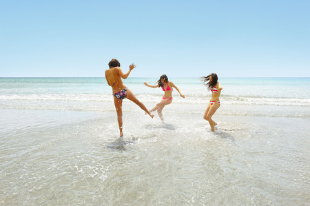 Three girls splashing each other