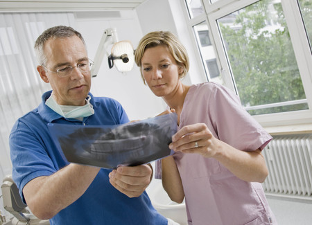 conferring: Dentist and assistant looking at x-rays