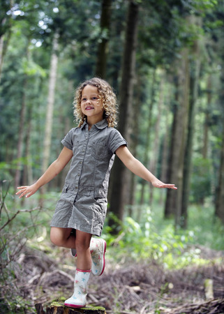 mischeif: Young girl balancing in woodland LANG_EVOIMAGES