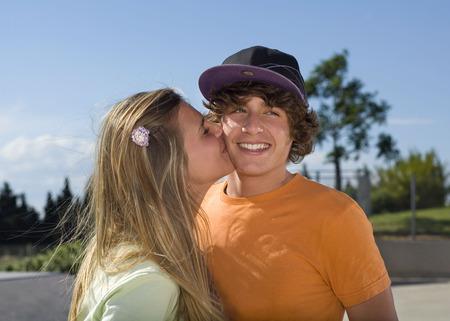 Teen girl kissing teen boy LANG_EVOIMAGES