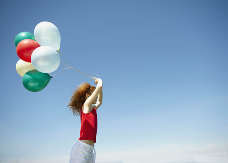 Young girl holding bunch of balloons LANG_EVOIMAGES