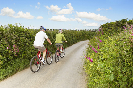 enthusiastically: Senior couple cycling up country lane