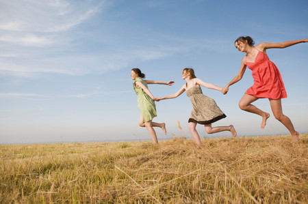 remoteness: Teenage girls running across a hay field
