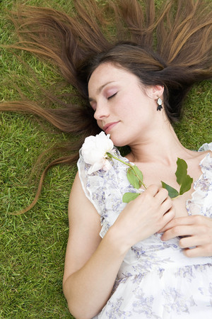 Woman laying on grass, holding rose LANG_EVOIMAGES