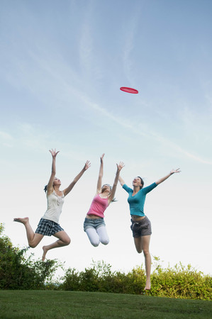 Teenage girls jump to catch a frisbee LANG_EVOIMAGES