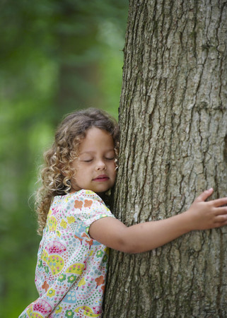 winchester: Young girl hugging tree eyes closed