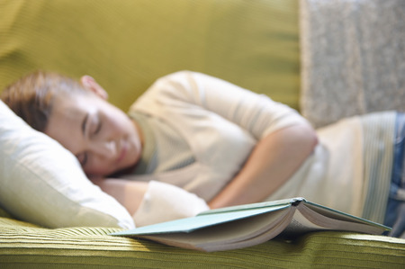 Young woman lying on couch, with book LANG_EVOIMAGES