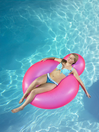 rejuvenated: Girl asleep on inflatable chair in pool