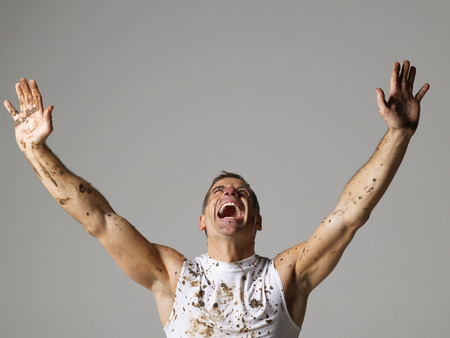 warming up: Joyous mud covered man with arms raised