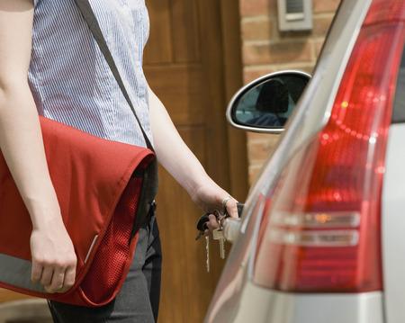 Woman using keys to open car door