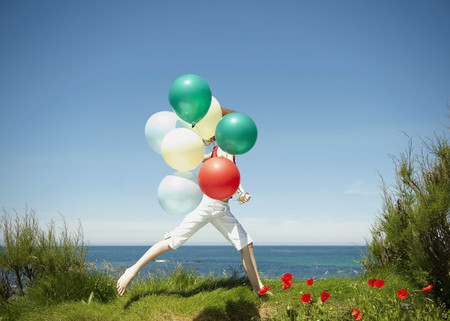Young girl running with balloons LANG_EVOIMAGES