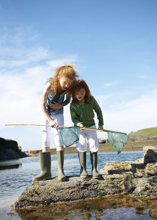 assembled: 2 girls looking in nets at rock pool LANG_EVOIMAGES