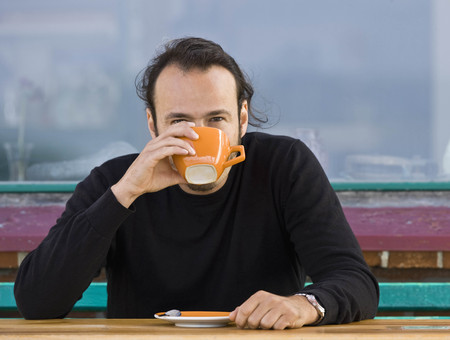 sipping: Man sitting at a cafe drinking coffee LANG_EVOIMAGES
