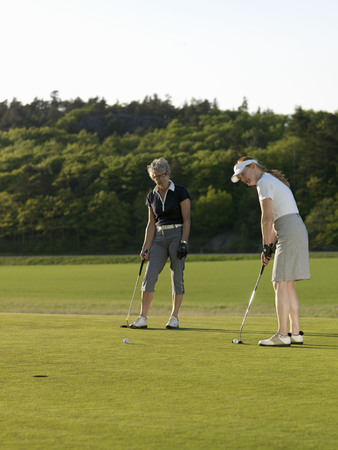 uncomplicated: Two women at golf green LANG_EVOIMAGES