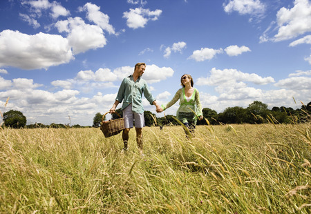 Couple holding hands with dog in field