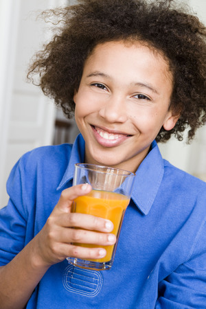 sipping: Boy smiling with a glass of orange juice LANG_EVOIMAGES