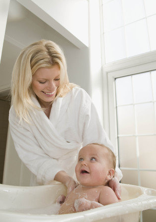 bathtime: A mother bathing her baby boy