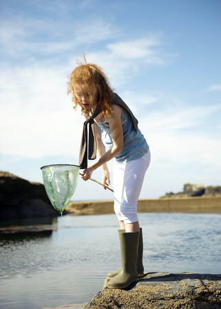 assembled: Young girl looking in net at rock pool LANG_EVOIMAGES