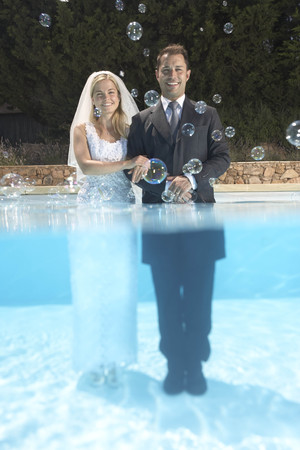 Bride and groom in pool with bubbles LANG_EVOIMAGES