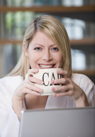 Female having a cappuccino at work LANG_EVOIMAGES