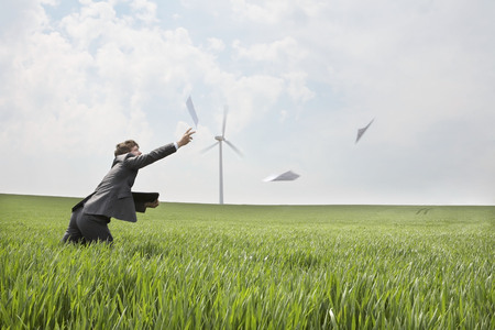 pursued: Businessman chasing papers on wind farm