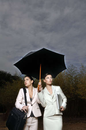 drizzling rain: 2 women under an umbrella