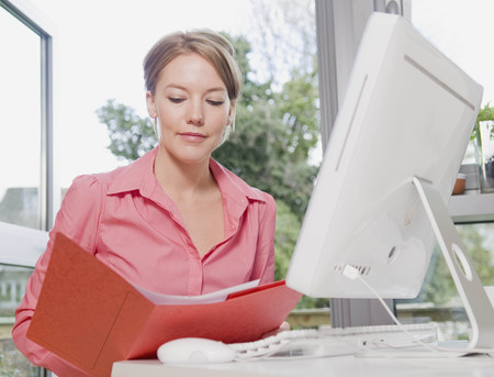 Female looking in a folder at her desk LANG_EVOIMAGES