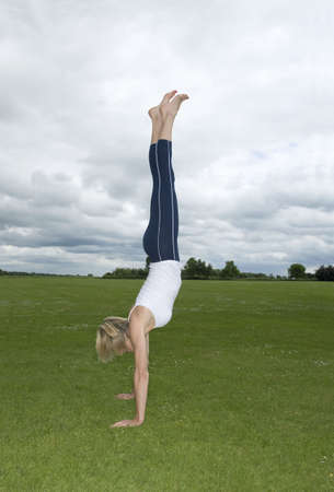 tetbury: Woman in park doing handstand LANG_EVOIMAGES