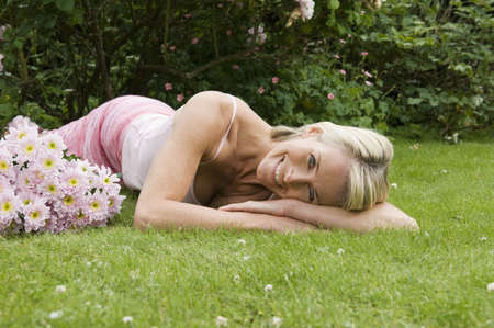 tetbury: Woman lying on grass with flowers