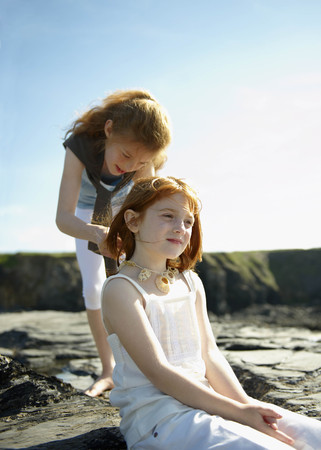 Girl putting shell necklace on sister