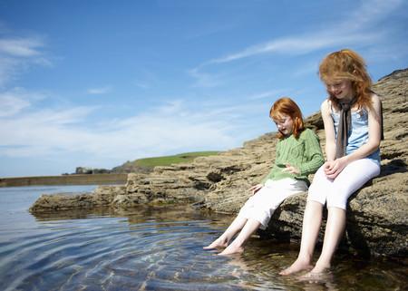 fulfill: 2 girls putting feet in rock pool