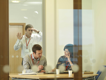 Man peering at office colleagues