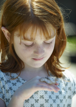 verticals: Young girl looking at butterfly