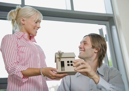 a meeting with a view to marriage: Couple holding a model of a house